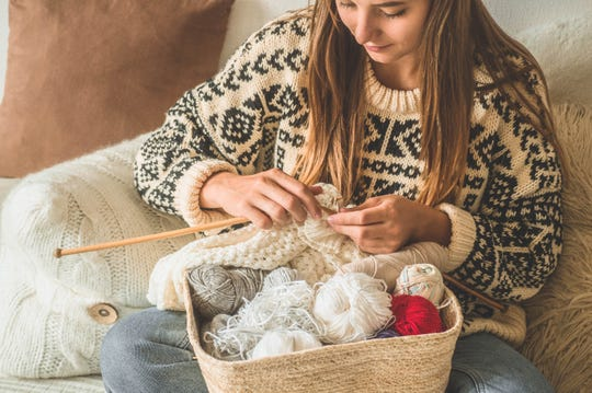 A young girl knits a sweater.