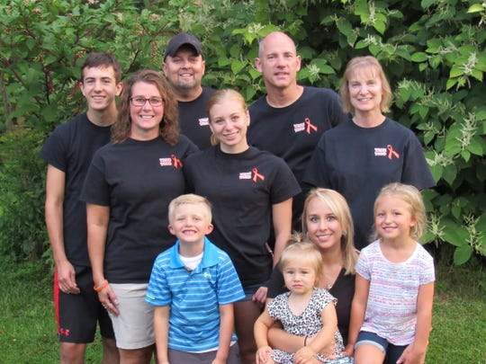 Todd Euen and his family have grown close to Mark Ecklund and his wife, Chris. They posed for this portrait: Front row, left to right: Kaiden Miller (Todd's grandson), Khloe Miller (granddaughter), Rachael Euen (daughter) and Kylie Miller (granddaughter). Middle row, left to right: Amy Euen (Todd's wife); Emily Euen (daughter); Chris Ecklund. Back row: Erik Euen (son); Todd Euen; Mark Ecklund.