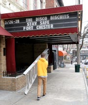 "Jack Ahearn, an employee at The Capitol Theater in Port Chester, walks away after placing a ""Stay Safe Port Chester"" message on the marquee, March 12, 2020. The Phil Lesh and Friends concert scheduled for this weekend has been postponed."