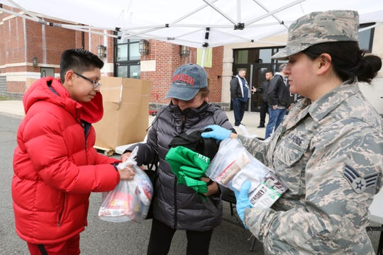 Senior Airman Paula Enriquez distributes food to Rosario Gutierrez of New Rochelle and her son James Sanchez, a student at Albert Leonard Middle School, March 12, 2020 at New Rochelle High School in New Rochelle, NY. Members of the National Guard have arrived in New Rochelle today to help deliver food and clean institutions in the coronavirus containment area.