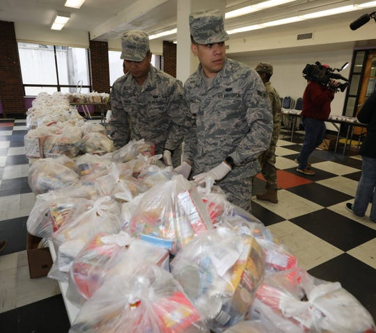 Members of the New York Air and Army National Guard unload bags of food at the New Rochelle Community Action Partnership, at the WestCOP building in New Rochelle, March 12, 2020.