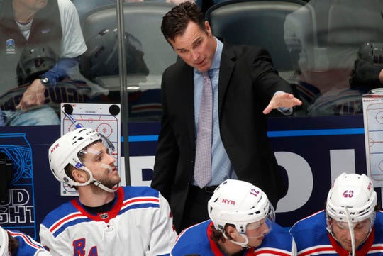 New York Rangers coach David Quinn confers with players on the bench during the first period of the team's NHL hockey game against the Colorado Avalanche on Wednesday, March 11, 2020, in Denver.