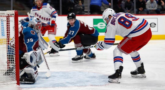 Colorado Avalanche goaltender Pavel Francouz, left, stops a shot off the stick of New York Rangers right wing Pavel Buchnevich during the second period of an NHL hockey game Wednesday, March 11, 2020, in Denver. (