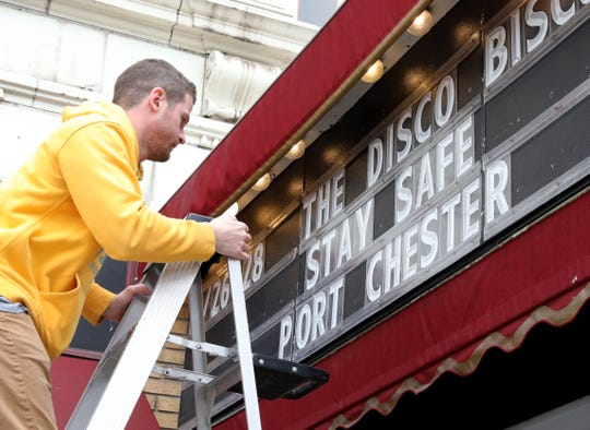 "Jack Ahearn, an employee at The Capitol Theater in Port Chester, places a ""Stay Safe Port Chester"" message on the marquee, March 12, 2020. The Phil Lesh and Friends concert scheduled for this weekend has been postponed."