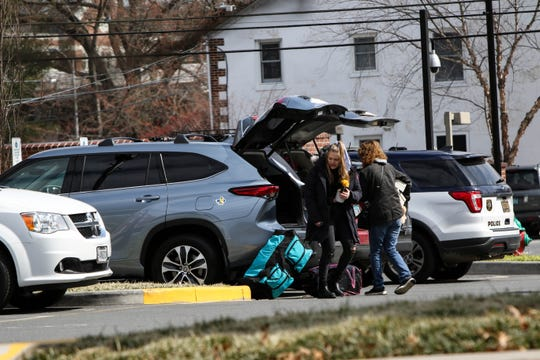A flow of people carrying bags and crates leave University of Delaware dorms Thursday after the school suspended in-person classes following the first presumptive positive case of coronavirus in the state. Classes will shift online beginning March 23 until further notice.