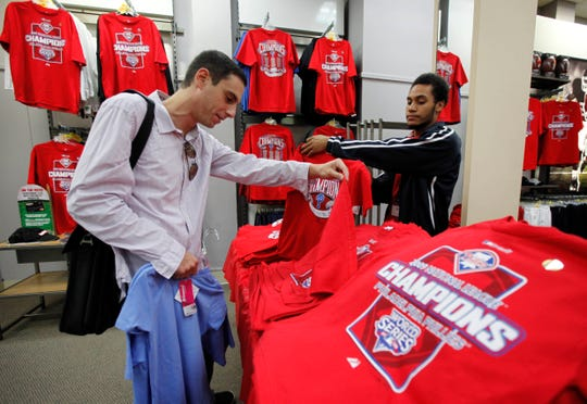 Philadelphia Phillies fans Michael R Cohen, left, looks for merchandise as salesperson Alberto Tilghman displays a shirt at a Modell's sporting goods store in Philadelphia, Thursday, Oct. 22, 2009.