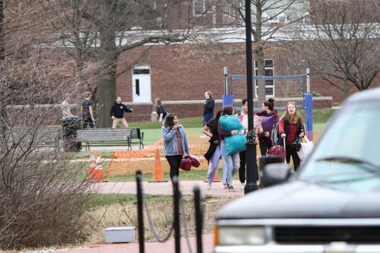 A flow of people carrying belongings leave University of Delaware dorms Thursday after the school suspended in-person classes following the first presumptive positive case of coronavirus in the state. Classes will shift online beginning March 23 until further notice.