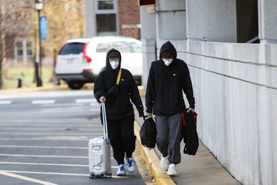 Amy San (left) and Yibo Lei, University of Delaware students, walk on campus wearing masks after the school suspended in-person classes following the first presumptive positive case of coronavirus in the state earlier this year.