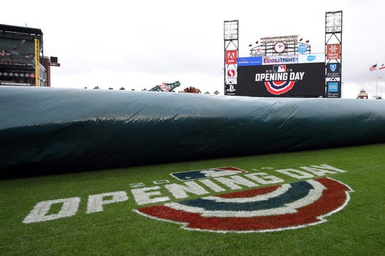 The Opening Day logo painted on the field is revealed as the tarp is removed before the game between the San Francisco Giants and the Tampa Bay Rays at Oracle Park.