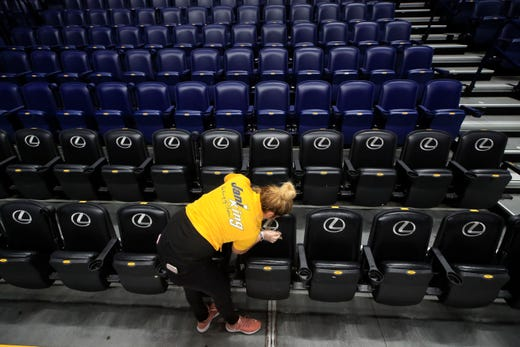 A worker cleans the seats after the announcement of the cancellation of the SEC Basketball Tournament at Bridgestone Arena on March 12, 2020 in Nashville.