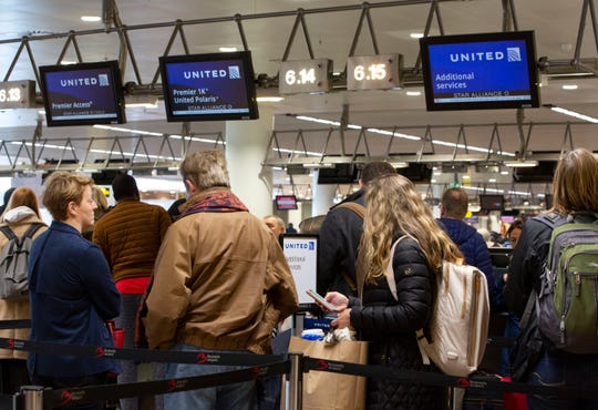 People wait to check in to a flight to Chicago at the United Airlines counter in the main terminal of Brussels International Airport in Brussels,, March 12, 2020. The European Union has slammed the new anti-virus travel ban announced by U.S. President Donald Trump on Wednesday.