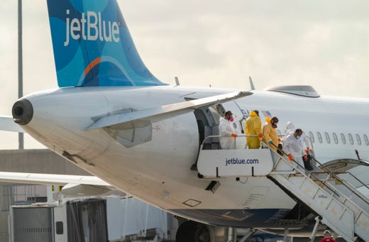 ACT Environmental Services crews clean a JetBlue plane after a flight from New York landed Wednesday night carrying a passenger who'd been infected with coronavirus at Palm Beach International Airport in West Palm Beach, Florida on March, 12, 2020.       (Via OlyDrop)