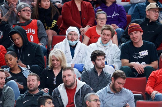 Portland Trail Blazers fans wear protective suits and gloves and masks mocking the COVID-19 coronavirus outbreak during the fourth quarter against the Phoenix Suns at the Moda Center on Mar 10, 2020.