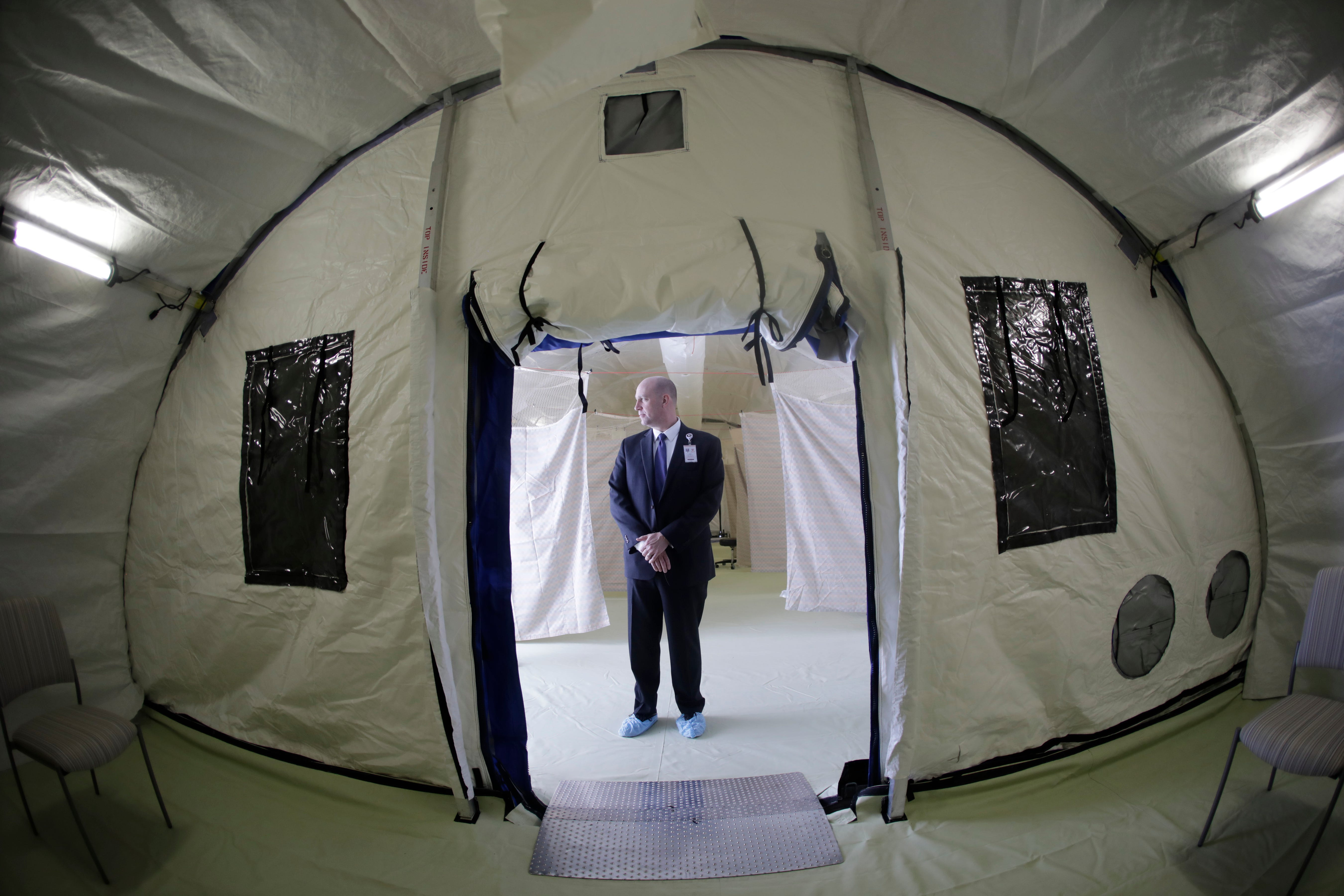 Philip Chaffee, senior director emergency management stands in a negative pressure tent outside the University of Utah's hospital, Monday, March 9, 2020, in Salt Lake City. The hospital is taking steps to limit the spread of the new coronavirus, including new visitor policies and the construction of outdoor negative pressure tents where people can be tested without having to go inside the hospital building.