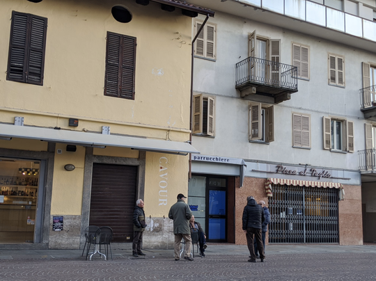 In the historic center of Bra, Italy: Men practicing the one-meter distance rule before all residents were banned from going out in public for non-essential reasons.