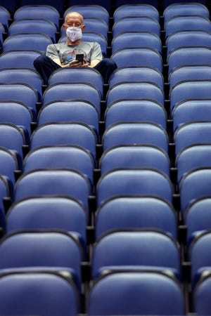 Mike Lemcke, from Richmond, Va., sits in an empty Greensboro Coliseum after the NCAA college basketball games were cancelled at the Atlantic Coast Conference tournament in Greensboro, N.C., Thursday, March 12, 2020. The biggest conferences in college sports all canceled their basketball tournaments, including the NCAA tournaments, because of the new coronavirus.