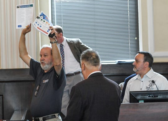 David Baker, director of Anderson County Emergency Management, holds up a flyer with information about COVID-19 during the Anderson County officials conference in the county council chambers Friday, March 13, 2020.