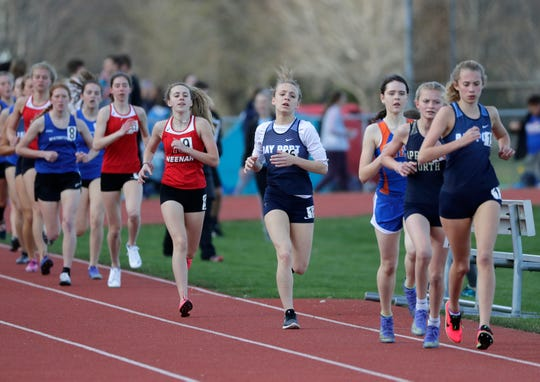 Athletes compete in the 1,600-meter run during the Neenah coed invitational track and field meet April 26, 2019, at Neenah High School.