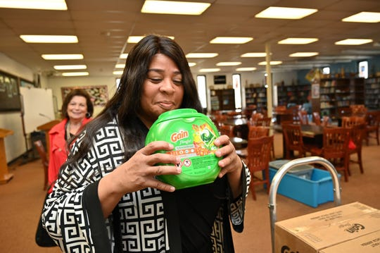 Asbury Park Board of Education President Angela Ahbez-Anderson checks out the aroma of the Gain pods that students will use to clean their clothes.