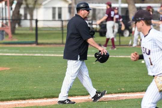 Hardin-Simmons coach Steve Coleman carries a pair of batting helmets back to the dugout after an inning against Schreiner at Hunter Field on Tuesday.