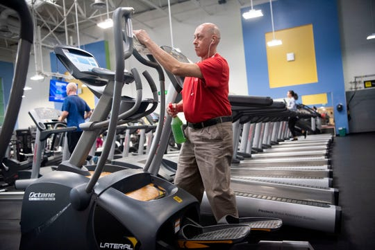 Staff member Carlos Ard disinfects workout equipment on Friday, March 13, 2020 at the YMCA in Battle Creek, Mich. Group classes at the YMCA are cancelled until March 22, however, the Health Enhancement Center and Wellness Center will remain open for regular business hours.