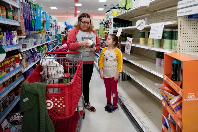 """Shauwna Holmes from Battle Creek shops for disinfectant wipes with her daughter Kaya Smith, 6, on Friday, March 13, 2020 at Target in Battle Creek, Mich. Holmes said Target had sold out of Clorox and Lysol, and she is skeptical of how well the Ever Spring brand will work. """"Never used it, I don't know effective it is, but we're going to try it and see,"""" said Holmes."""