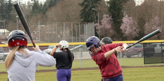 South Kitsap's Lynden Wolf (right) takes warm-up swings during a practice at the high school on March 12.