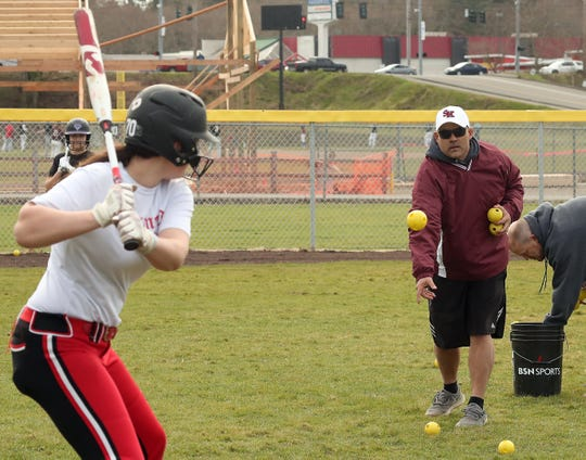 South Kitsap softball coach Bobby Lawrence pitches whiffle balls to his team as its warms up for a scrimmage against JV at South Kitsap High School in Port Orchard on March 12, 2020.