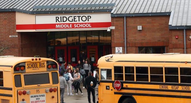 Students exit Ridgetop Middle School in Silverdale at the end of classes on Friday, March 13, 2020.
