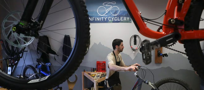 Bryan Wells moves a bike into position to perform the rest of the maintenance after checking the suspension of it at Infinity Cyclery in Poulsbo on Friday.