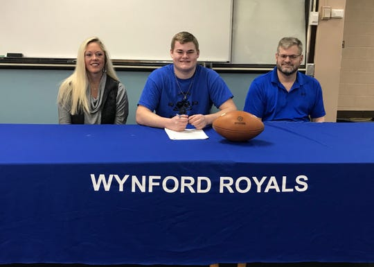 Wynford's Gavin Leffler signs his letter of intent to continue his football career at Tiffin University alongside his parents, Carmen and Dan.