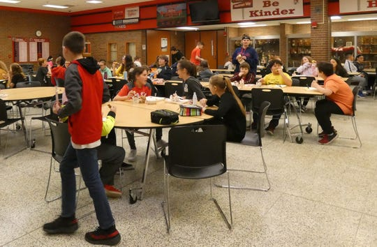 Students eat lunch at Bucyrus Secondary School on Friday, the final day of classes before the district closed for at least three weeks as part of the state's efforts to battle COVID-19.