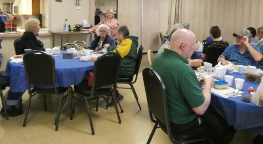 Cassie Herschler, standing at rear, explains to seniors dining at the Crawford County Council on Aging on Friday that while the center has canceled all activities indefinitely, the daily congregate meals will continue.