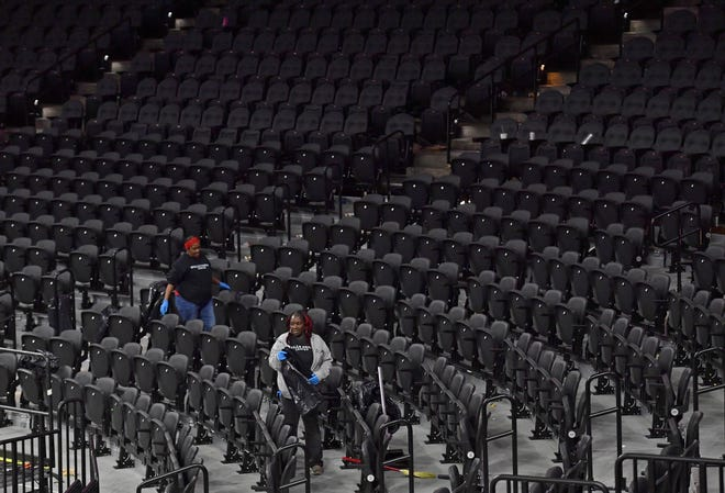 Employees clean the seating area after Wednesday's game between the 76ers and Detroit Pistons at Wells Fargo Center.