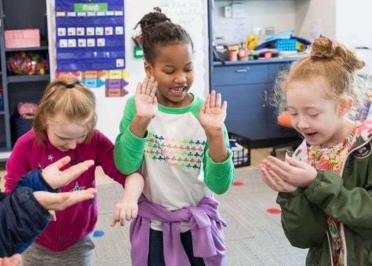 Briar, Alameyah, and Allie try to get the glitter off their hands and bodies after shaking hands. The three girls participated in an experiment by kindergarten teacher Mr. Christy that illustrated how easily germs can spread.