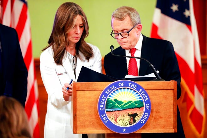 Ohio Gov. Mike DeWine signs an order banning groups of 100 or more people, along with Dr. Amy Acton, left, the head of the Ohio Department of Health, during a press conference updating the public on COVID-19 on Thursday, March 12, 2020 in Columbus, Ohio. A fifth case of COVID-19, the disease caused by the novel coronavirus, was confirmed in Ohio earlier Thursday.  (Doral Chenoweth/The Columbus Dispatch via AP)
