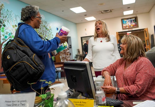 Janey Holleman, center, and Terrie Nolen, right, react when Stephanie Mason, left, shows off the disinfectant wipes she was able to snag at Kroger at Ajax Senior Center in Clarksville, Tenn., on Thursday, March 12, 2020.