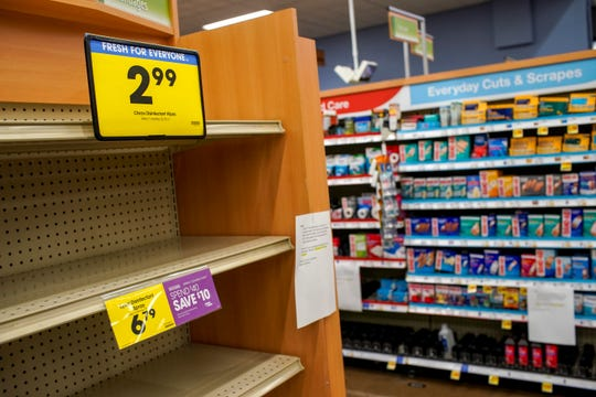 Empty shelves where disinfectant wipes and sanitary supplies used to be sit next to picked shelves at Kroger on Madison Street in Clarksville, Tenn., on Thursday, March 12, 2020.