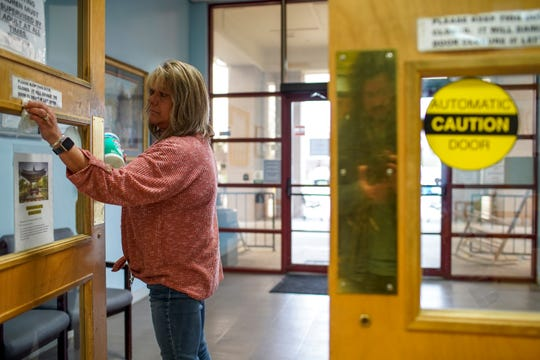 Terrie Nolen wipes down doors and handles for the entrance way at Ajax Senior Center in Clarksville, Tenn., on Thursday, March 12, 2020.