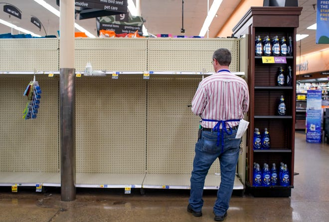 A Kroger employee checks a ravaged shelf at Kroger on Madison Street in Clarksville, Tenn., on Thursday, March 12, 2020.