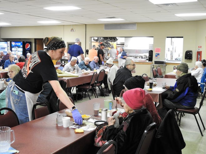 Michelle Bassett serves people Friday at the Coshocton Senior Center. The number of people eating at the center was a lot lower than most days. The center is ending activities as of Monday, but keeping its in-house and home delivered meals for senior citizens of the community.