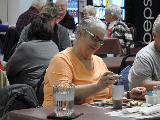 Rossann Davis seasons her food Friday during lunch at the Coshocton Senior Center. The registered nurse said she's not fearful of the COVID-19 coronavirus, but she's also aware of the importance of washing your hands and other precautionary measures.