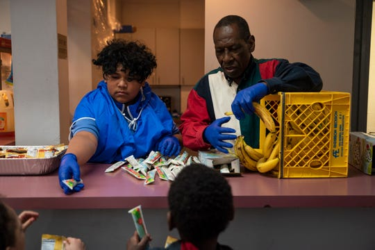 Richard Hughes (right) hands out bananas to youth members on March 13, 2020 at the Willkie House in Des Moines. Willkie House staff have temporarily switched from using vinyl disposable gloves to nitrile ones for better fit and sanitation to prevent the spread of COVID-19.