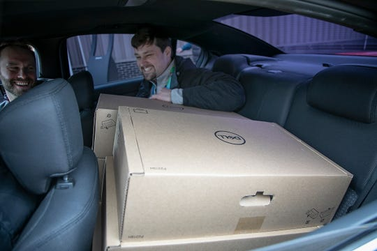 Joshua Flitton of Quicken Loans Mortgage Services, right, smiles as he is piled in the backseat with 6 monitors for he and his colleagues as they prepare to work remotely due to the Coronavirus scare Thursday, March 12, 2020. Rock Central organized the computer pick-up in a lot in Detroit.