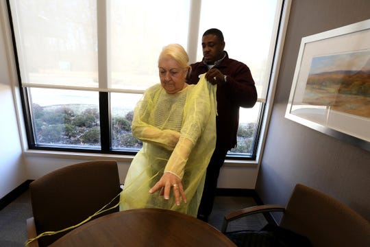 Johanna Mannone, 79,  gets help from Donald Tolliver, the executive director of WellBridge of Rochester Hills, putting her gown on before seeing her husband, Mike, on Friday for a onetime, specially arranged visit.