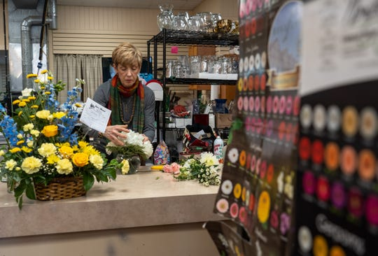 Patricia York works on an arrangement for a customer at Jim's Florist on March 13 in Warren. The business has lost some revenue due to events being canceled because of coronavirus concerns.