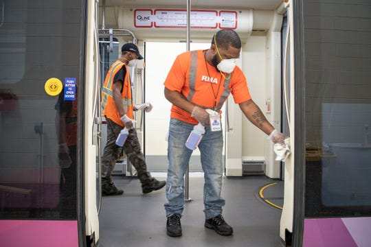 Terrance Royal, night supervisor for RNA Facilities Management, the company that contracts with M1 Rail disinfects the door handle on a QLine train at Penske Tech Center in Detroit, Wednesday, March 11, 2020. Mohammad Hamad of account manager said the company has increased the frequency of cleaning and disinfecting the touch points on the trains.