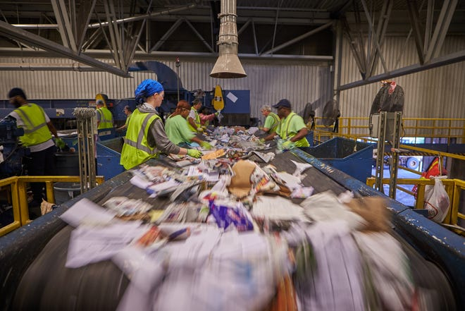Workers sort materials at Kent County Recycling and Education Center in Grand Rapids.