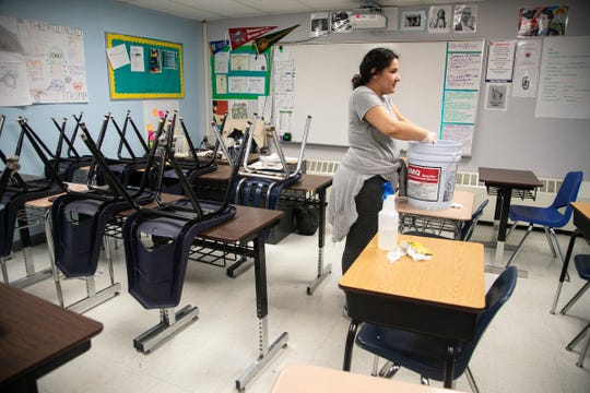 Detroit's Cesar Chavez Academy High School alumni Elizabeth Cardona, 21, a senior in social work at Saginaw Valley State University, chips into deep clean her alma mater while she too is on break as schools prepare for the Coronavirus threat on March, 13, 2020.