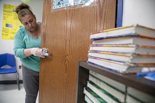 Detroit's Cesar Chavez Academy High School custodian Sonia Mercado works on deep cleaning the economics classroom as schools prepare for the Coronavirus threat on March, 13, 2020.